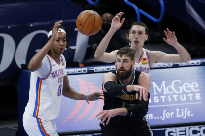 Memphis Grizzlies center Jonas Valanciunas (17) passes the ball away from Oklahoma City Thunder center Moses Brown (9) and forward Aleksej Pokusevski (17) during the second half of an NBA basketball game, Sunday, March 14, 2021, in Oklahoma City. (AP Photo/Garett Fisbeck)