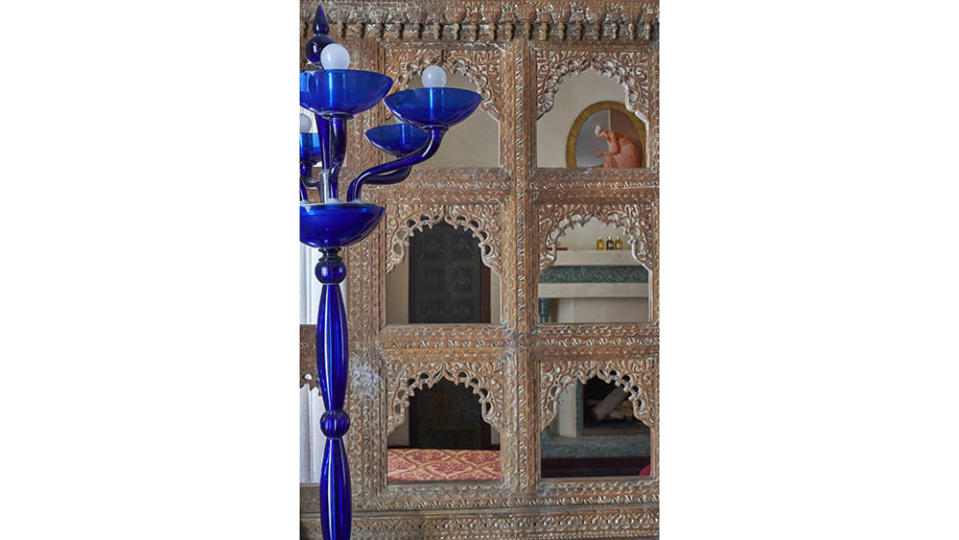 The eclectic furnishings include this Murano glass lamp and carved wooden screens the owner bought in India. - Credit: Jean Cazals