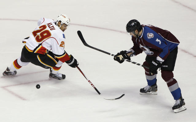 "FILE - In this Feb. 28, 2013, file photo, Calgary Flames right wing Akim Aliu loses control of the puck as the blade of his stick breaks off, while Colorado Avalanche's Ryan O'Byrne defends during the first period of an NHL hockey game in Denver. Former NHL forward Aliu expects ""big change"" in hockey after a meeting with top league executives Tuesday. Aliu met with NHL Commissioner Gary Bettman and deputy commissioner Bill Daly in Toronto to discuss his allegation that former Flames coach Bill Peters used a racial slur several times during the 2009-10 season while the two were with the Chicago Blackhawks' top minor league affiliate in Rockford, Ill. The Flames investigated Alius claim, and Peters resigned last Friday. Peters apologized to the Flames and general manager Brad Treliving for using ""offensive language"" in Rockford. (AP Photo/David Zalubowski, File)"