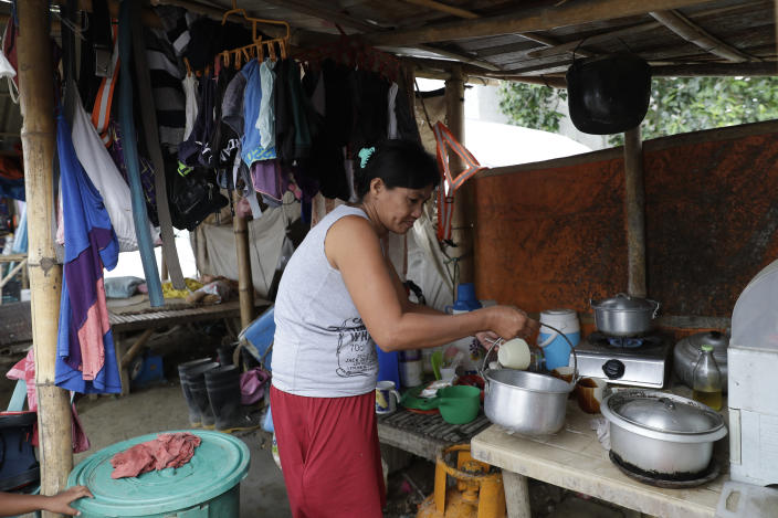 Luisa Silva, a former resident of Taal volcano, arranges her kitchen at their tent at a relocation site in Balete, Batangas province, Philippines, on Sunday, Jan. 10, 2021. Some families are still living in tents and have resorted to taking odd jobs to make a living as the government has prevented them from returning back to their homes almost a year after Taal volcano erupted on Jan. 12, 2020. The eruption displaced thousands of villagers living near the area and delivered an early crisis this year for one of the world's most disaster-prone nations a couple of months before the COVID-19 pandemic broke in the country. (AP Photo/Aaron Favila)