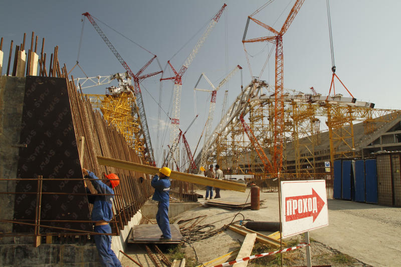 """In this photo taken Thursday, Aug. 9, 2011, cranes surround the Olympic Stadium at the Olympic Park which is under construction in the Black Sea resort of Sochi, southern Russia with the poster reading """"Passage"""" on the right. Sochi will host the 2014 Winter Olympics. The idea of holding the Winter Olympics in Sochi once seemed as much of a long shot as a gold medal for Jamaica's bobsledders, a city that few outside Russia had ever heard of, in a country notorious for inefficient construction, corruption, and a byzantine visa regime. (AP Photo/Igor Yakunin)"""