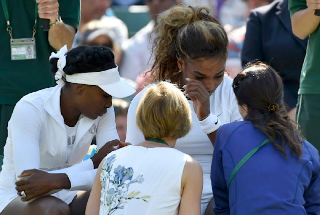 Serena Williams of the U.S. (C) appears unwell before retiring from her women's doubles tennis match with Venus Williams of the U.S. (L) against Kristina Barrois of Germany and Stefanie Voegele of Switzerland at the Wimbledon Tennis Championships, in London July 1, 2014. REUTERS/Toby Melville (BRITAIN - Tags: SPORT TENNIS)