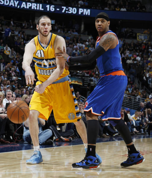 Denver Nuggets center Kosta Koufos, left, passes the ball around New York Knicks forward Carmelo Anthony in the third quarter of the Nuggets' 117-94 victory in an NBA basketball game in Denver on Wednesday, March 13, 2013. Anthony left the game with sore knees ater the play. (AP Photo/David Zalubowski)