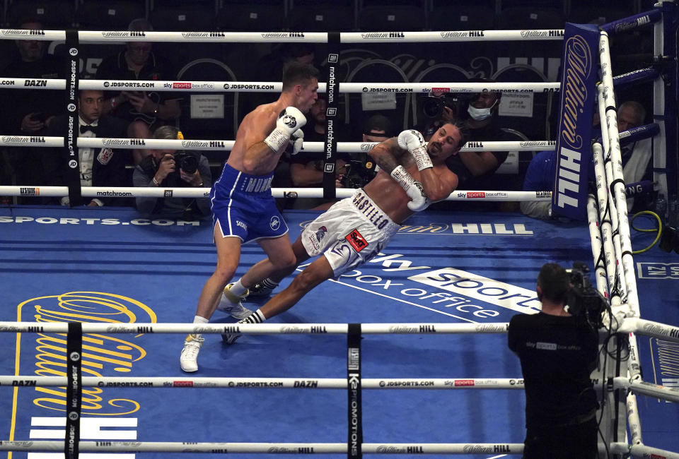 """Britain's Callum Smith, left, knocks down Dominican Republic's Lenin Castillo during their Light-Heavyweight contest at the Tottenham Hotspur Stadium, in London, Saturday, Sept. 25, 2021. Castillo was taken to hospital after being carried out of the ring on a stretcher following a devastating knockout by British opponent Callum Smith. Event promoter Eddie Hearn says the 33-year-old Castillo was """"responsive"""" after needing treatment by medical staff in the ring at Tottenham Hotspur Stadium in one of the fights on the undercard of the world heavyweight title bout between Anthony Joshua and Oleksandr Usyk. Castillo's legs appeared to spasm after he hit the canvas and referee Bob Williams quickly called off the fight in the second round.(Nick Potts/PA via AP)"""