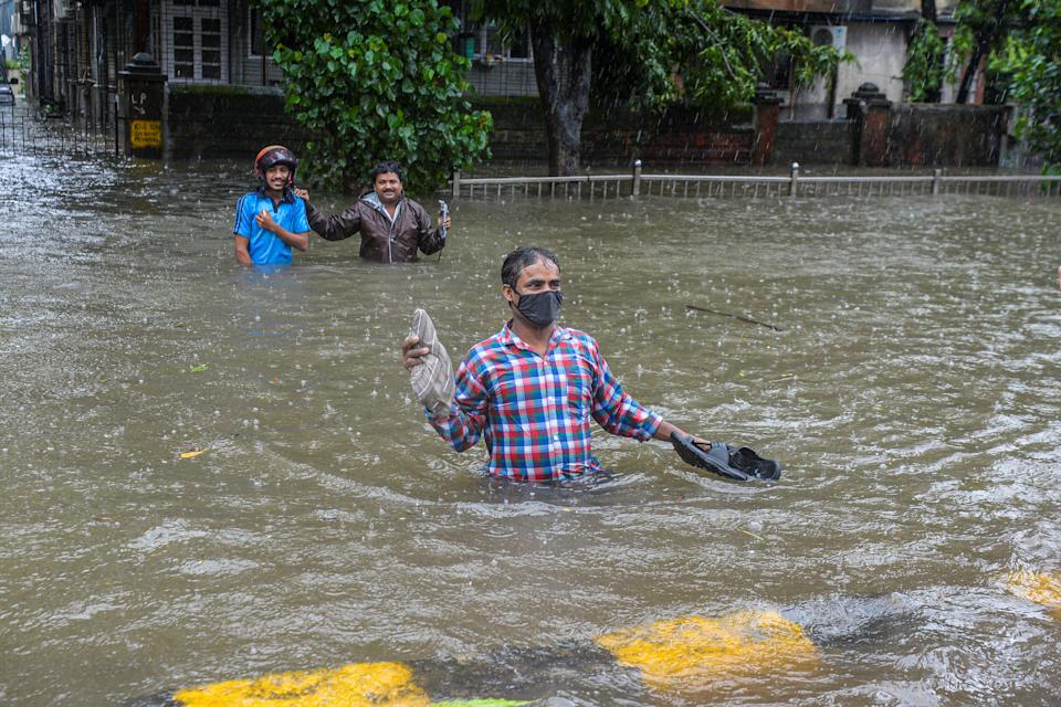 Commuters wade in waist deep water crossing a flooded road during a heavy monsoon rain in Mumbai on August 4, 2020. (Photo by Indranil MUKHERJEE / AFP) (Photo by INDRANIL MUKHERJEE/AFP via Getty Images)