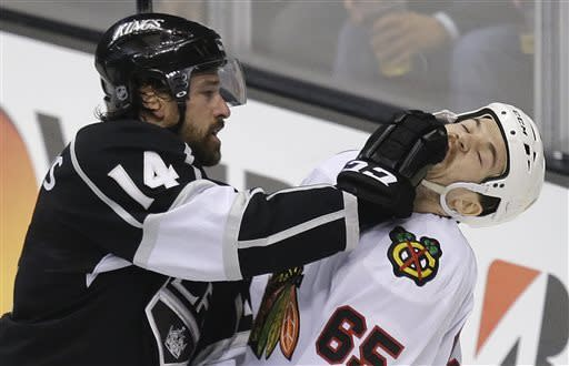 Los Angeles Kings right wing Justin Williams (14) fights with Chicago Blackhawks center Andrew Shaw (65) during the second period of Game 3 of the NHL hockey Stanley Cup playoffs Western Conference finals, Tuesday, June 4, 2013 in Los Angeles. (AP Photo/Jae C. Hong)