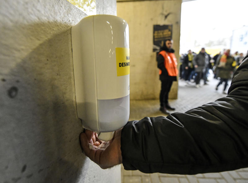 FILE - In this Feb. 29, 2020, file photo, a fan washes his hands at a new disinfection station in the stadium prior the German Bundesliga soccer match between Borussia Dortmund and SC Freiburg in Dortmund, Germany. In large masses, there is no system that can effectively prevent another person from giving germs to a second individual, said Philip Tierno, a clinical professor of pathology at New York University's Grossman School of Medicine. (AP Photo/Martin Meissner, File)