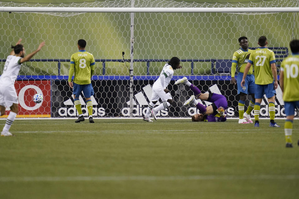 Seattle Sounders goalie Stefan Frei, right, tumbles to the turf as the Portland Timbers score in the first half of an MLS soccer match Thursday, Oct. 22, 2020, in Seattle. (AP Photo/Elaine Thompson)