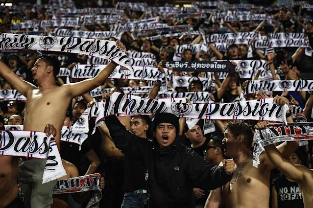 Thai football fans wave scarves in unison during a World Cup qualifying match: now the domestic league has been hit by match-fixing claims (AFP Photo/LILLIAN SUWANRUMPHA)