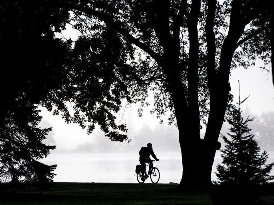 A cyclist makes their way in heavy fog beside Dow's Lake in Ottawa, Wednesday, Oct. 6, 2021. (Justin Tang/Canadian Press - image credit)