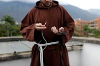 Venezuelan priest Luis Antonio Salazar gets ready to record a video for his social media on a rooftop in Caracas
