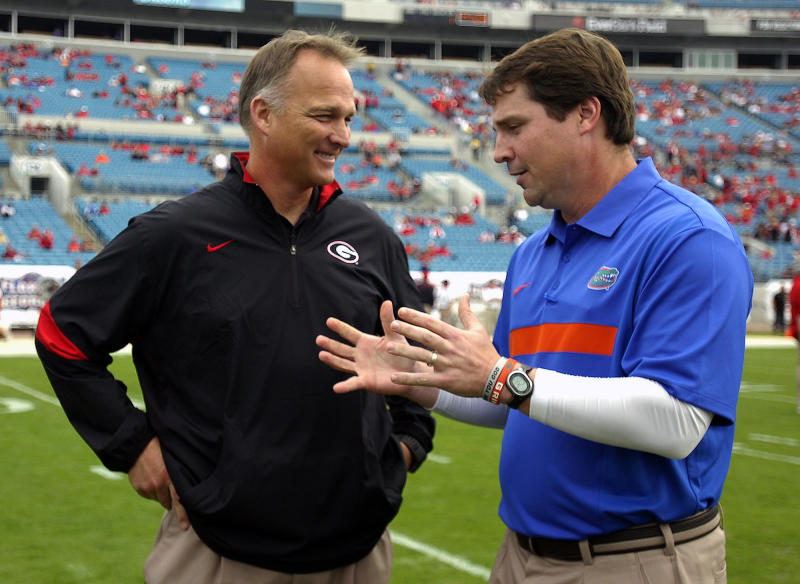 FILE - In this Oct. 29, 2011, file photo, Florida head coach Will Muschamp, right, and Georgia head coach Mark Richt talk before their NCAA college football game in Jacksonville, Fla. If the No. 12 Bulldogs can beat one decent team _ ONE! _ they will be in line to return to the Southeastern Conference championship game. Of course, it's been a while since they beat a team the caliber of third-ranked Florida. The two schools meet on Saturday in Jacksonville. (AP Photo/Stephen Morton, File)