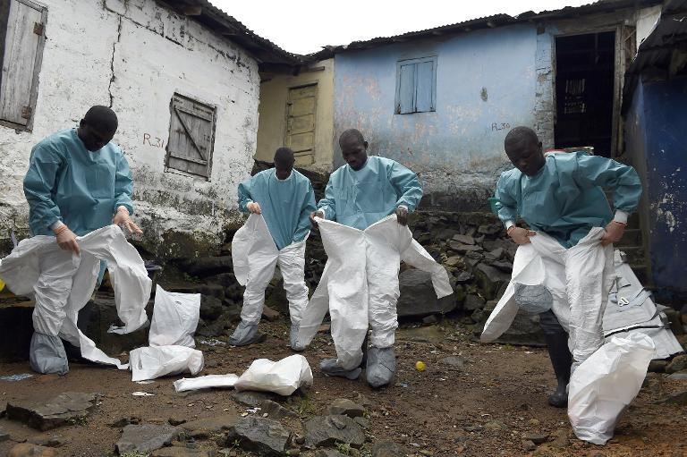 Medical staff members put on protective suits before collecting the corpse of an Ebola victim, in Monrovia, on September 29, 2014