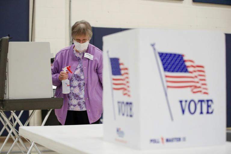 An election observer cleans voting booths during a Democratic presidential primary election at the Kenosha Bible Church gym in Kenosha, Wisconsin, on April 7, 2020
