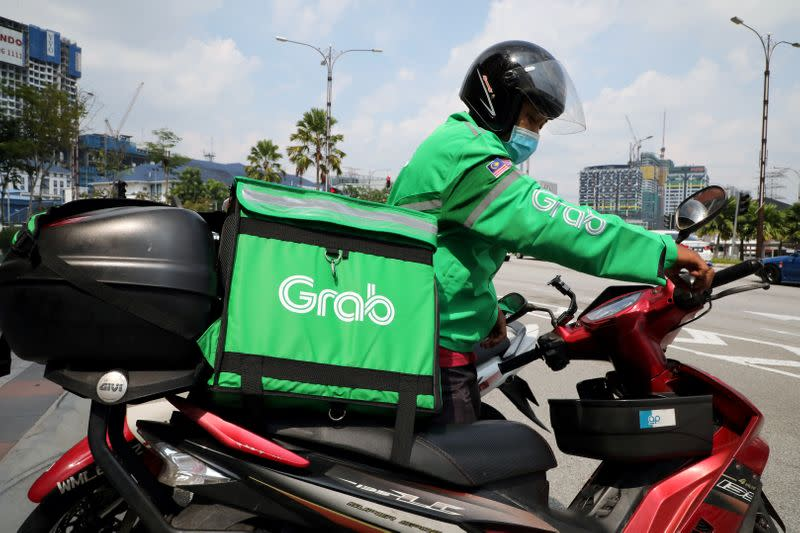 FILE PHOTO: A GrabFood rider gets ready for a delivery outside a shopping mall, amid the coronavirus disease (COVID-19) outbreak in Kuala Lumpur