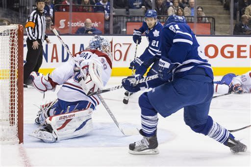 Toronto Maple Leafs' Phil Kessel, right, scores on Montreal Canadiens goaltender Peter Budaj during second-period NHL hockey game action in Toronto, Saturday, April 13, 2013. (AP Photo/The Canadian Press, Chris Young)