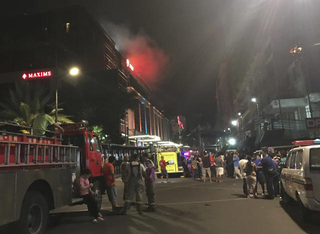 <p>Emergency responders and onlookers gather outside as smoke rises from the Resorts World Manila complex, early Friday, June 2, 2017, in Manila, Philippines. (Photo: Bullit Marquez/AP) </p>