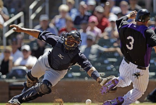 Colorado Rockies' Michael Cuddyer (3) scores as Seattle Mariners catcher Miguel Olivo, left, dives for the throw from the outfield on a single by Todd Helton during the first inning of a spring training baseball game on Tuesday, April 3, 2012 in Scottsdale, Ariz. (AP Photo/Marcio Jose Sanchez)