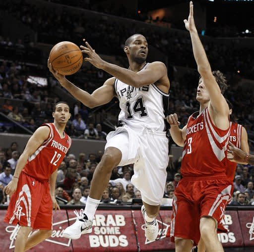 San Antonio Spurs' Gary Neal (14) drives between Houston Rockets' Goran Dragic (3), of Slovenia, and Kevin Martin (12) during the first quarter of an NBA basketball game, Wednesday, Jan. 11, 2012, in San Antonio. (AP Photo/Eric Gay)
