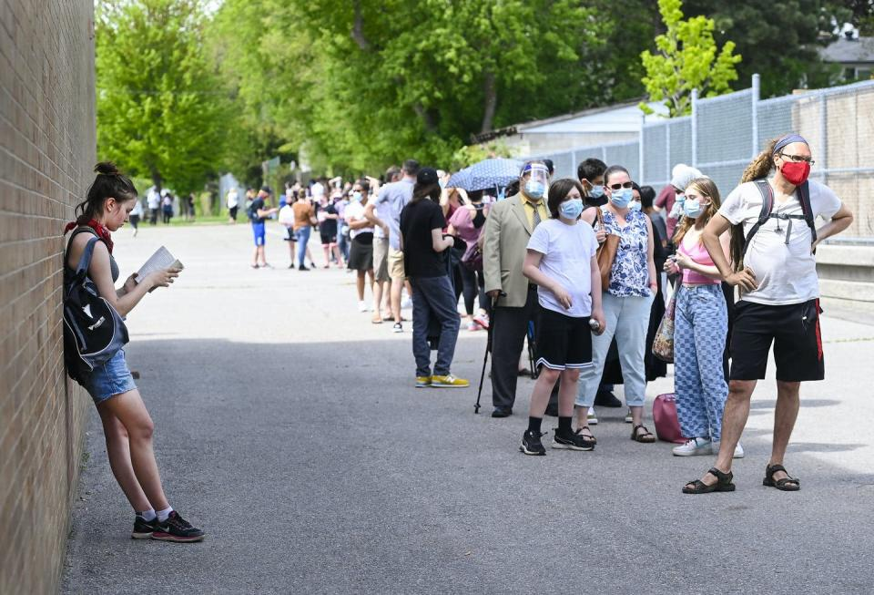 """<span class=""""caption"""">Families and youth aged 12 and older lined up for a COVID-19 vaccine at Gordon A Brown Middle School in Toronto in May.</span> <span class=""""attribution""""><span class=""""source"""">THE CANADIAN PRESS/Nathan Denette </span></span>"""