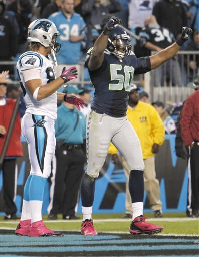 Seattle Seahawks' K.J. Wright (50) reacts as Carolina Panthers' Greg Olsen (88) stands by after the Panthers' incomplete pass on fourth down during the fourth quarter of an NFL football game in Charlotte, N.C., Sunday, Oct. 7, 2012. The Seahawks won 16-12. (AP Photo/Bob Leverone)