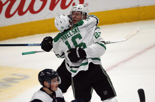 Dallas Stars center Joe Pavelski, front, hugs defenseman Esa Lindell after he scored the winning goal in overtime of an NHL hockey game against the Colorado Avalanche Tuesday, Jan. 14, 2020, in Denver. Dallas won 3-2 in overtime. (AP Photo/David Zalubowski)