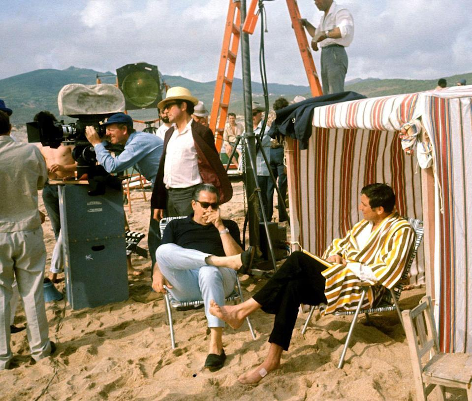 <p>George Lazenby sitting on a beach with producer Albert R. Broccoli while filming 'On Her Majesty's Secret Service', 1969. Director Peter R. Hunt is standing just behind them.</p>