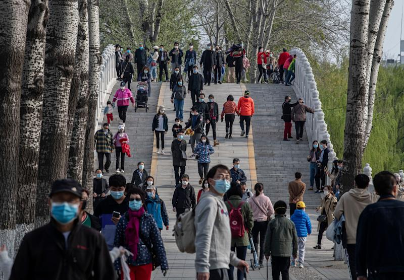 People wear protective masks as they walk while enjoying the spring weather at a park in Beijing, China. (Photo: Kevin Frayer via Getty Images)