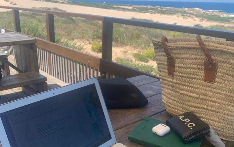 Amy Thomson has taken to working at cafes overlooking the beach