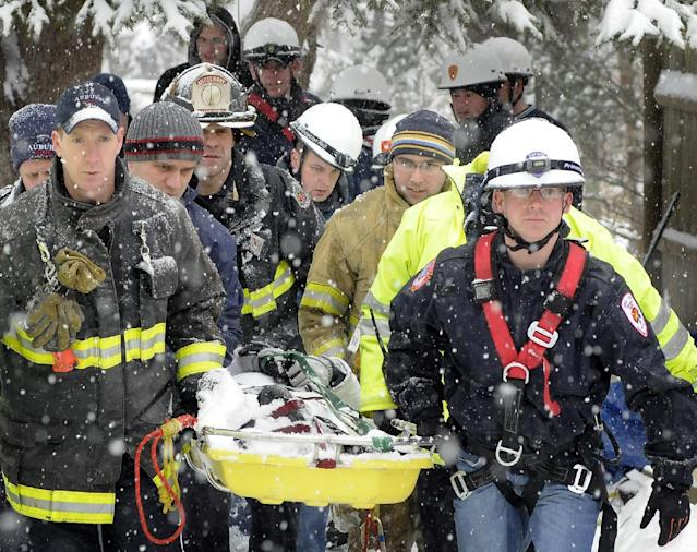 A winter storm that dropped close to a foot of snow in some areas of Massachusetts made driving treacherous Wednesday Feb. 5, 2014 and prompted closures and school cancellations around the state. Members of a regional technical rescue team carry an injured 13-year-old girl, Trisha King, to a waiting ambulance after bringing her up a 20-30 foot embankment in Oxford, Mass. during a snow storm Wednesday. The girl and a friend were playing behind her house when both slid down the steep hill and King's leg was injured in the fall. The team performed a slope evacuation and the girl was stable with a leg and hip injury when transported by Oxford EMS. (AP Photo/Worcester Telegram & Gazette, Rick Cinclair)