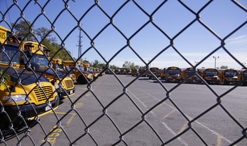 Boston school busses sit idle behind a chain link fence at Veolia Transportation, the city's school bus contractor, in Boston, Tuesday, Oct. 8, 2013. About 600 school bus drivers have gone on strike affecting most of the school district's 33,000 students. (AP Photo/Stephan Savoia)
