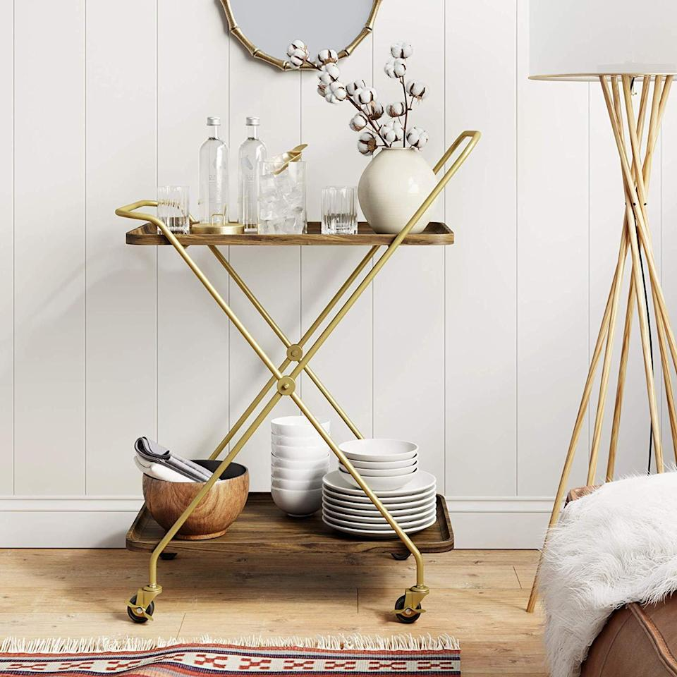 """<h3>Modern Rolling Bar Cart</h3><br>This streamlined tray-top cart is one effortless-looking bar solution for tight spaces (and budgets). <br><br><strong>Nathan James</strong> Mid-Century Rolling Bar Serving Cart with 2-Tier Trays, $, available at <a href=""""https://amzn.to/3bHR6C7"""" rel=""""nofollow noopener"""" target=""""_blank"""" data-ylk=""""slk:Amazon"""" class=""""link rapid-noclick-resp"""">Amazon</a>"""