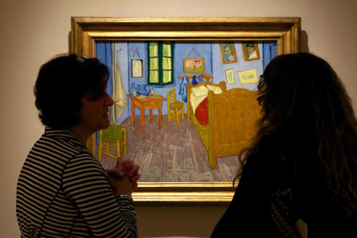 """In this Oct. 8, 2013 photo, women discuss Vincent van Gogh's """"The Bedroom at Arles,"""" on display at The Phillips Collection in Washington. In the midst of the shutdown of federally funded museums, the private Phillips Collection is launching the first major exhibition of Vincent van Gogh's artwork in Washington in 15 years. (AP Photo/Molly Riley)"""