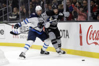 Winnipeg Jets' Anthony Bitetto, left, presses Los Angeles Kings' Trevor Lewis (22) against the boards during the second period of an NHL hockey game Saturday, Nov. 30, 2019, in Los Angeles. (AP Photo/Marcio Jose Sanchez)