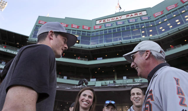 San Francisco Giants right fielder Mike Yastrzemski, left, talks with family and friends after batting practice prior to a baseball game against the Boston Red Sox at Fenway Park in Boston, Tuesday, Sept. 17, 2019. Yastrzemski is the grandson of Red Sox great and Hall of Famer Carl Yastrzemski. (AP Photo/Charles Krupa)