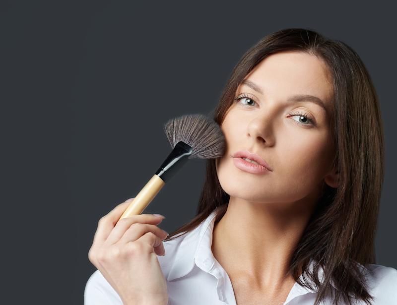 Closeup portrait of woman with makeup brushes near face