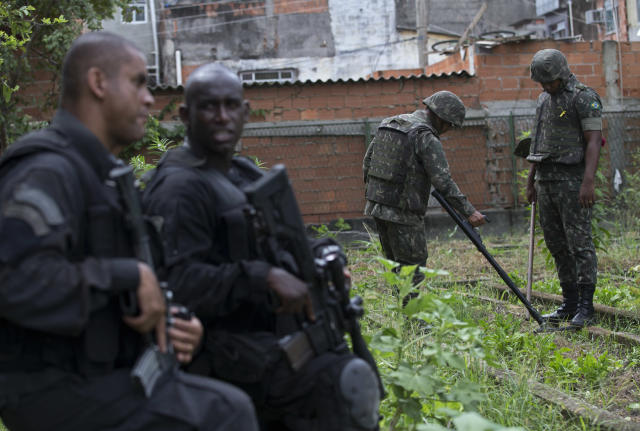 """Special Police Operations Battalion (BOPE) officers stand guard, as army soldiers look for weapons with the aid of a metal detector during an operation in the Mare slum complex, ahead of its """"pacification,"""" in Rio de Janeiro, Brazil, Wednesday, March 26, 2014. Elite federal police and army troops will be sent to the city to help quell a wave of violence in so-called """"pacified"""" slums. Recent attacks on police bases in the favelas is raising concerns about an ambitious security program that began in 2008, in part to secure the city ahead of this year's World Cup and the 2016 Olympics. (AP Photo/Silvia Izquierdo)"""