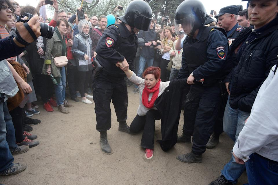 Riot police officers detain a participant of an opposition rally.