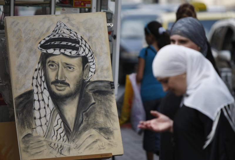 A Palestinian woman stands by a drawing of late Palestinian leader Yasser Arafat, displayed on a street corner in the West Bank city of Ramallah, Thursday, July 5, 2012. Palestinian President Mahmoud Abbas has said he's willing to exhume the body after doctors said they found elevated levels of the radioactive agent polonium-210 on clothing reportedly worn by Arafat before his death in November 2004. However, Abbas aide Nimr Hamad said Thursday the Palestinian leader first wants to send experts to Europe to learn more from the Swiss lab and to the French military hospital where Arafat died. (AP Photo/Majdi Mohammed)