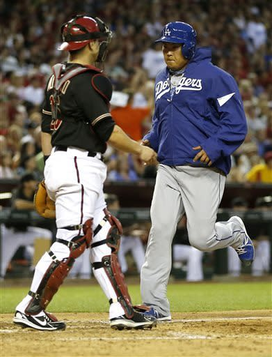 Los Angeles Dodgers' Hyun-jin Ryu, right, of South Korea, scores on a hit by Matt Kemp as Arizona Diamondbacks' Miguel Montero watches during the sixth inning of a baseball game on Saturday, April 13, 2013, in Phoenix. (AP Photo/Matt York)