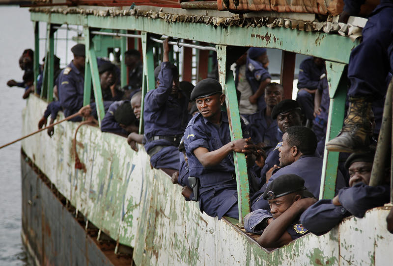 """Police Nationale du Congo officers who fled Goma when M23 rebels took over the city Nov. 18 2012, return on a barge to the port of Goma, eastern Congo, Friday Nov. 30, 2012. The police force were returning to resume control on Friday, as had been agreed by the regional bloc. Rebels in Congo believed to be backed by Rwanda postponed their departure Friday from the key eastern city of Goma by 48 hours for """"logistical reasons,"""" defying for a second time an ultimatum set by neighboring African countries and backed by Western diplomats. The delay raises the possibility that the M23 rebels don't intend to leave the city they seized last week, giving credence to a United Nations Group of Experts report which argues that neighboring Rwanda is using the rebels as a proxy to annex territory in mineral-rich eastern Congo. (AP Photo/Jerome Delay)"""
