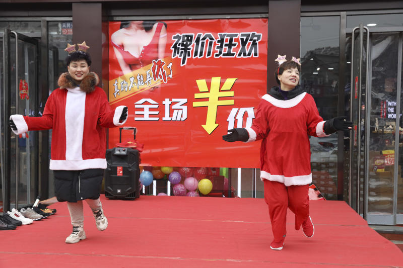 In this photo Saturday, Dec. 22, 2018, photo, sales staff from an apparel shop dance wearing Christmas themed costumes to promote a year end sales in Zhangjiakou in northern China's Hebei province. At least four Chinese cities and one county have restricted Christmas celebrations this year. Churches in another city have been warned to keep minors away from Christmas, and at least ten schools nationwide have curtailed Christmas on campus, The Associated Press has found. (AP Photo/Ng Han Guan)