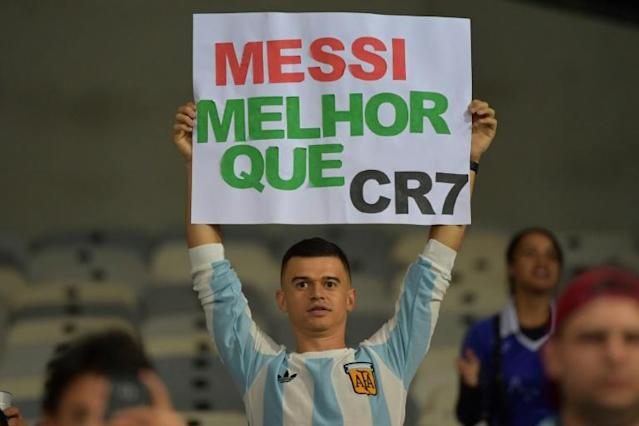 "A fan of Argentina displays a placard reading ""Messi better than CR7"" at the start of the Copa America match against Paraguay in June (AFP Photo/Luis ACOSTA)"