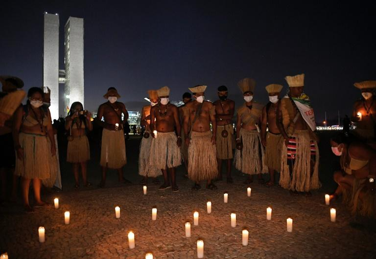 Members of different indigenous tribes hold a candlelit vigil outside the Supreme Court Building in Brasilia, on August 24, 2021