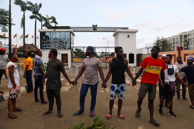 Demonstrators hold hands as they gather near the Lagos State House