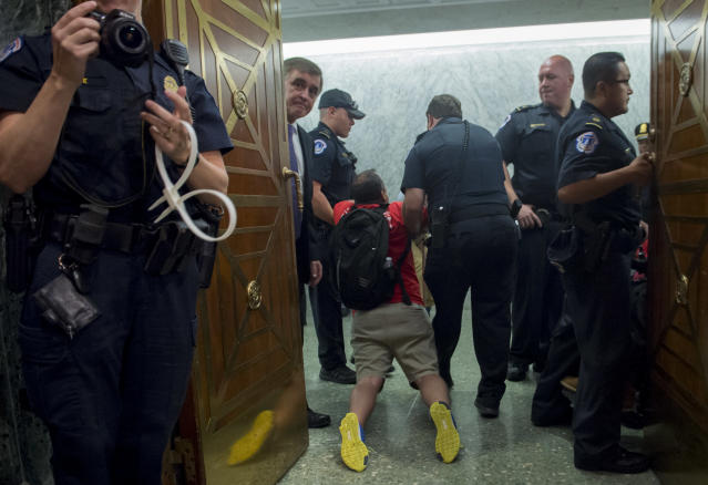 <p>US Capitol Police remove protestors from the US Senate Committee on Finance hearing on the Graham-Cassidy-Heller-Johnson Proposal on reforming health care on Capitol Hill in Washington, DC, September 25, 2017.(Photo: Saul Loeb/AFP/Getty Images) </p>