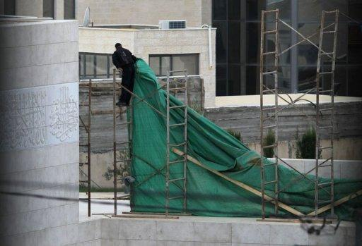 A Palestinian worker placesa plastic tarp around the mausoleum of the late Palestinian leader Yasser Arafat