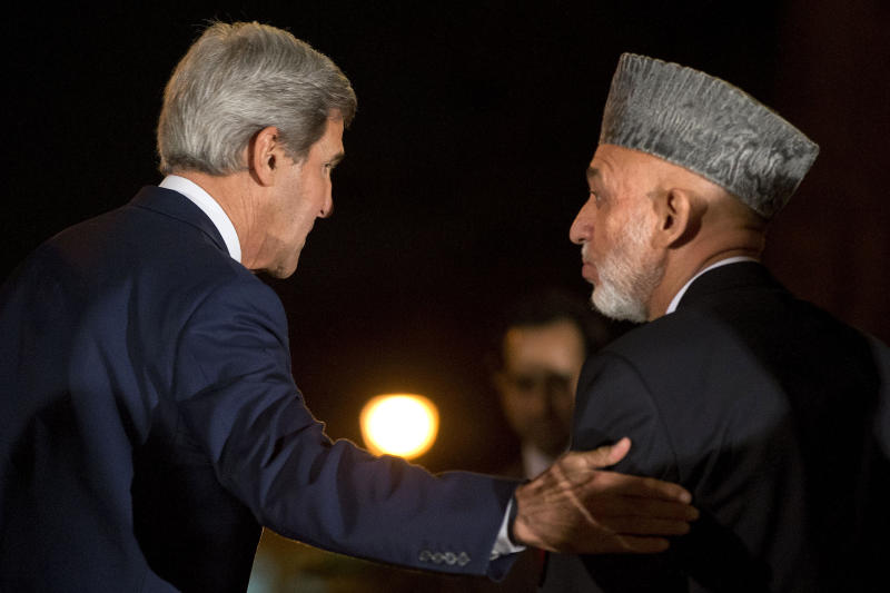 U.S. Secretary of State John Kerry, left, turns with Afghan President Hamid Karzai as they say goodbye at the end of a news conference announcing a tentative agreement between the two countries at the Presidential Palace during Kerry's unannounced stop in Kabul, Afghanistan, on Saturday, Oct. 12, 2013, as a deadline approaches for a security deal about the future of U.S. troops in the country. (AP Photo/Jacquelyn Martin, Pool)