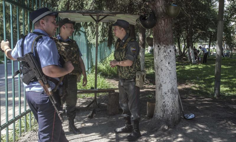 In this Monday, July 23, 2012 photo, security personnel guard a hotel where ethnic Circassian refugees from Syria stay at in Nalchik, Russia. Some 340 ethnic Circassians from Syria have come to Russia's Caucasus region this year. Czarist troops and Cossacks expelled hundreds of thousands of Circassians in the 1860s in what some historians call a genocide and an ethnic cleansing. (AP Photo/Misha Japaridze)