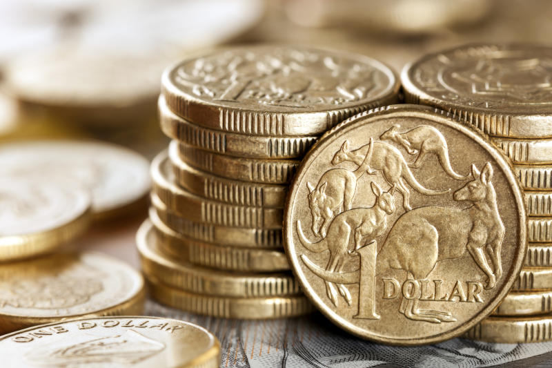 Stacks of Australian one dollar coins. Focus on front coin.